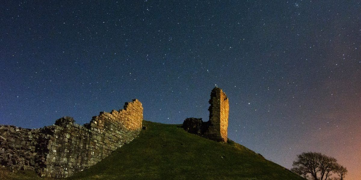 Harbottle Castle at night with starry skies