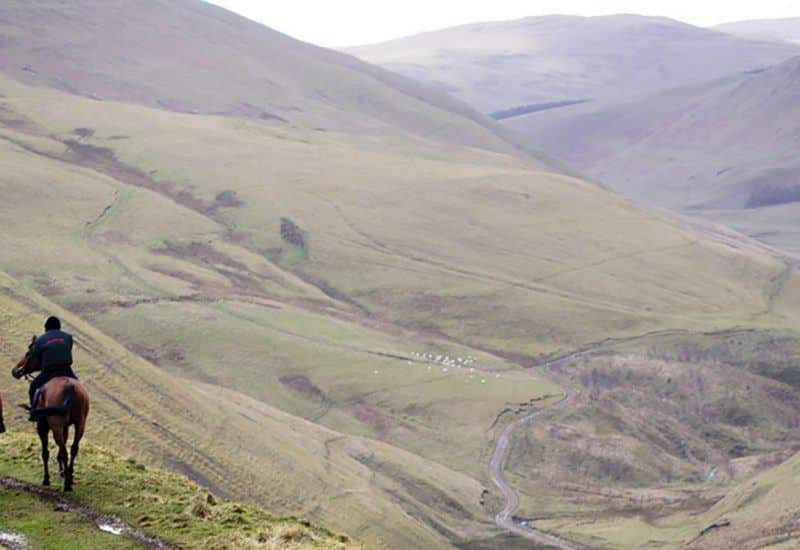 Two horses and riders in the Northumberland National Park