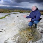 Stan Beckensall showing a cup and ring marked stone