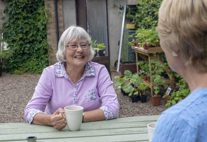 an elderly woman enjoying a cup of tea sat at a wooden table