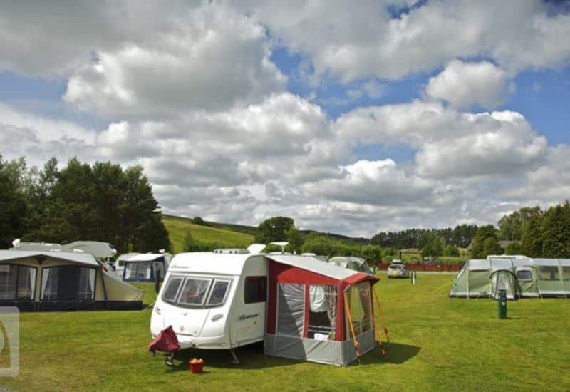 a photo of caravan and tents in a field