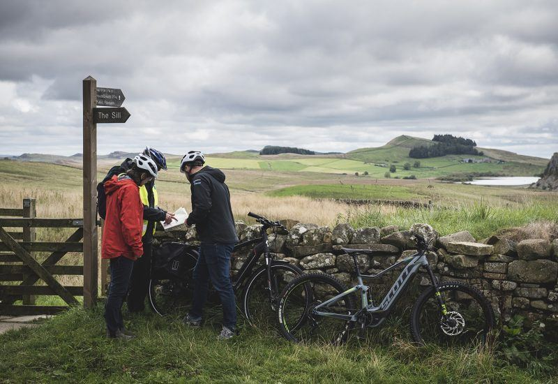 Three people checking a map while riding E-bikes near Hadrian's Wall
