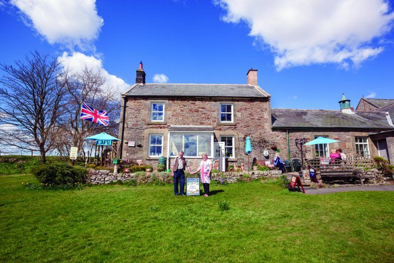 A photo of the exterior of Elsdon tea room on a bright, sunny day. The two owners are standing in front of the tea room.