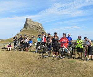 a group of cyclists smiling with holy island priory behind them