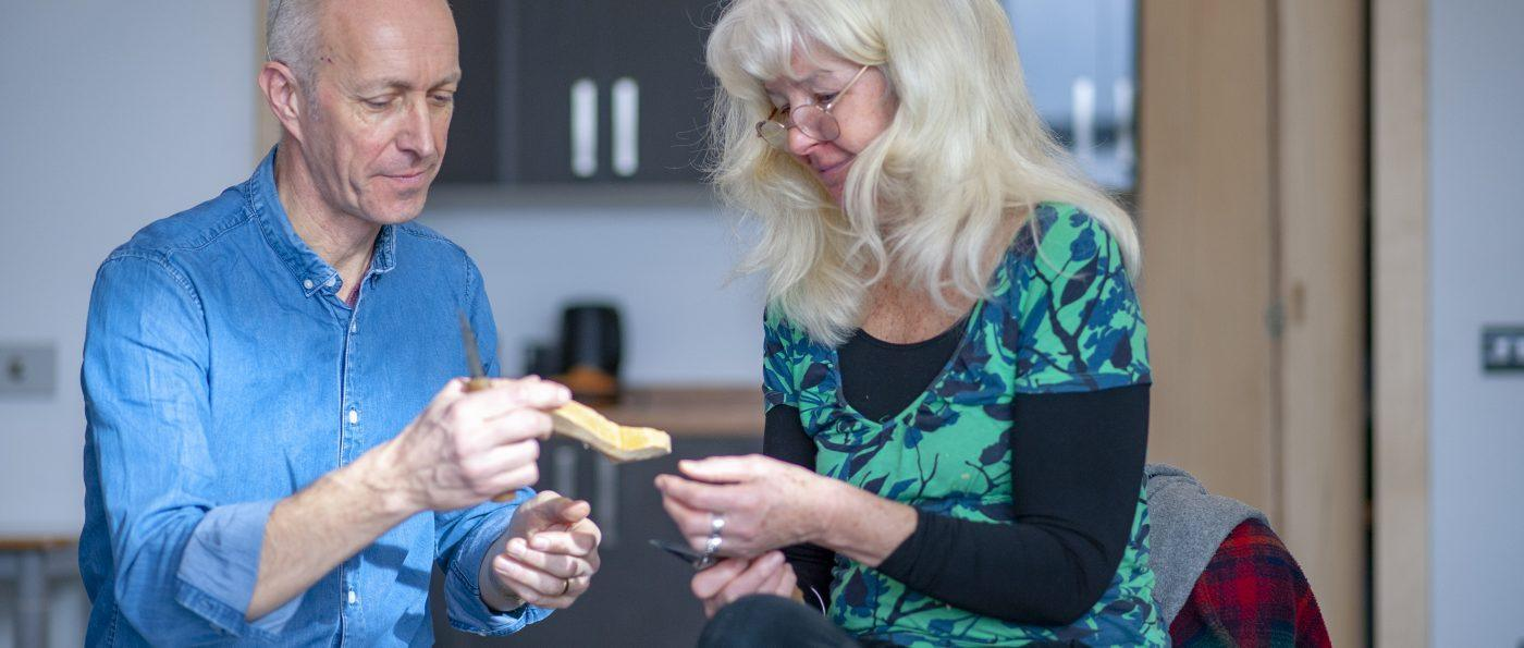 A course leader helps a woman at a spoon carving workshop