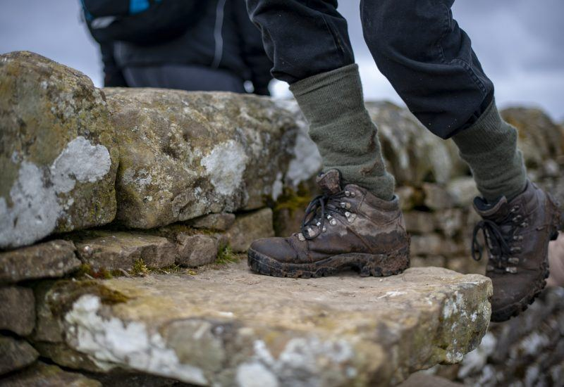 a close up image of walking boots crossing a drystone wall