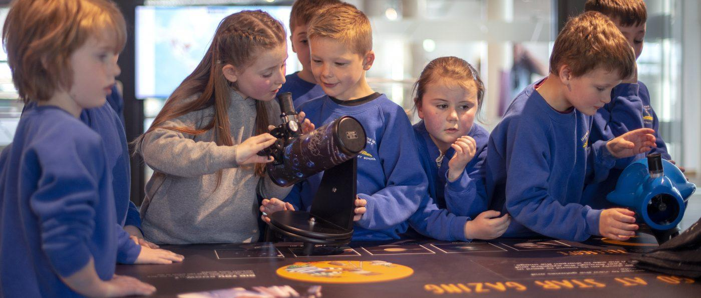 a group of school children looking through small telescopes at The Sill: National Landscape Discovery Centre