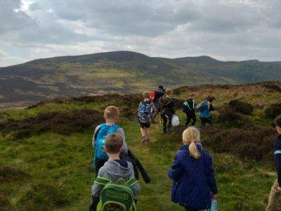 School children walking away from the camera in the Simonside hills