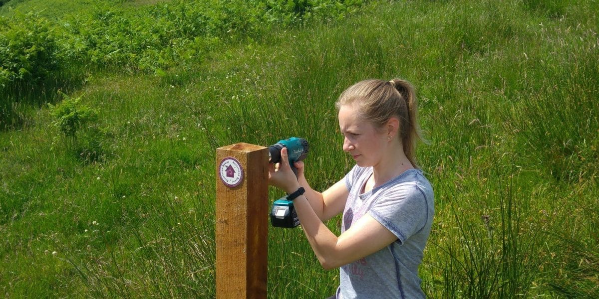 A young volunteer adding directional signage to a finger post in the national park