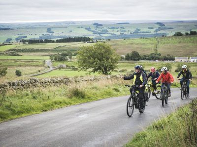 Three people riding Ebikes near Hadrian's Wall