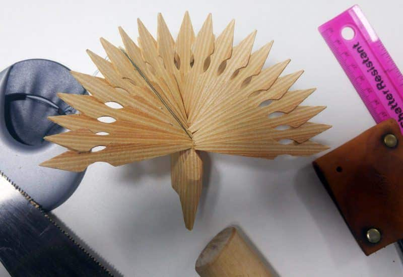 A photograph of a wooden fan bird with its wing fanned out.