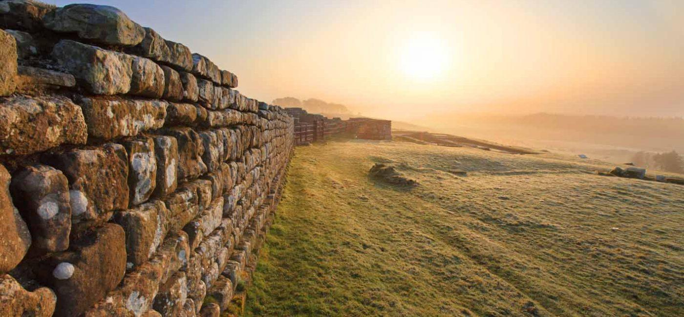 An early morning photograph of Hadrian's Wall with the sun rising