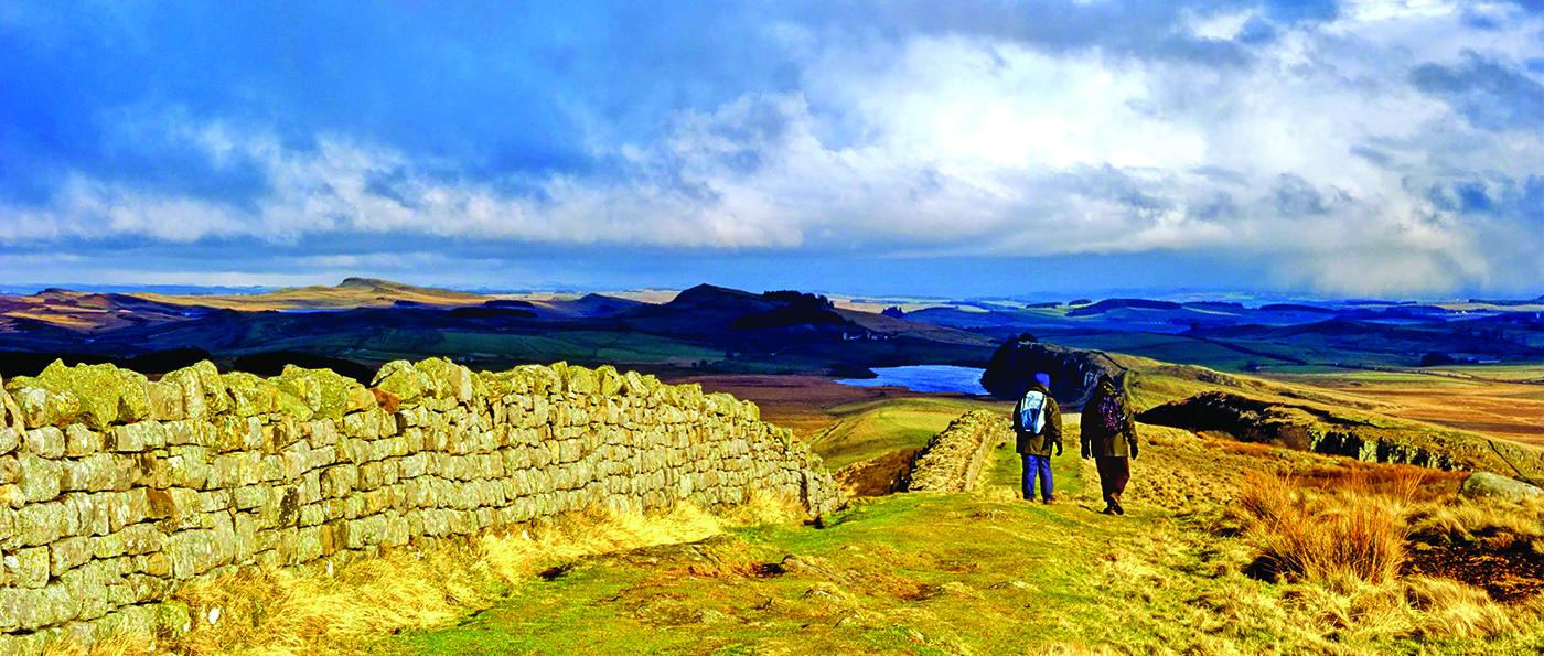 Walkers walking alongside Hadrian's Wall at Winshield Crags