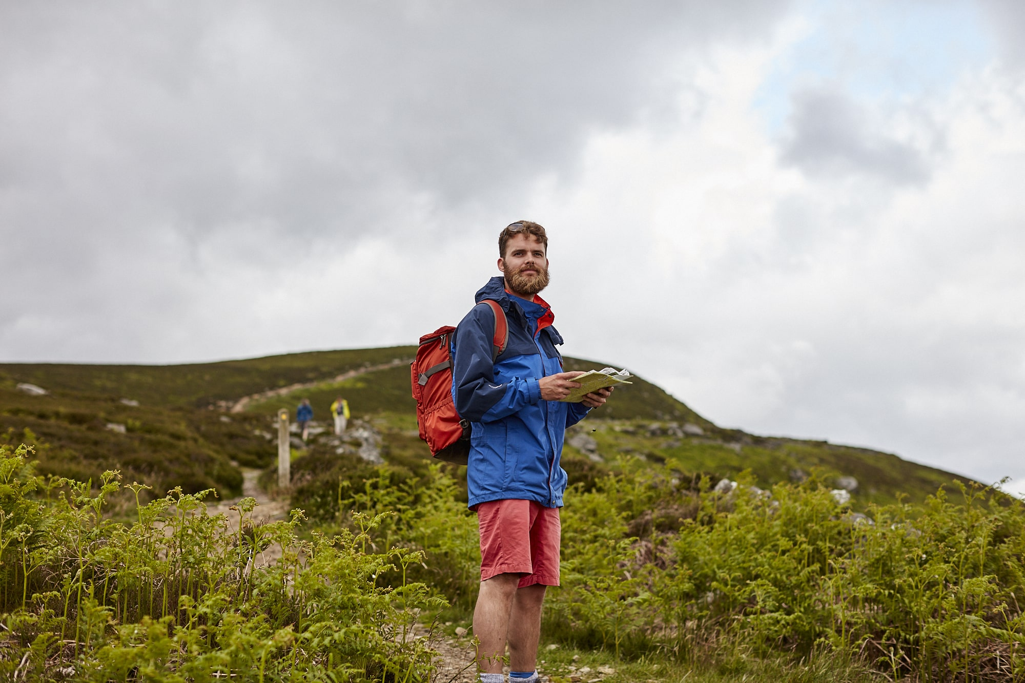 A young man reading a map in the hills