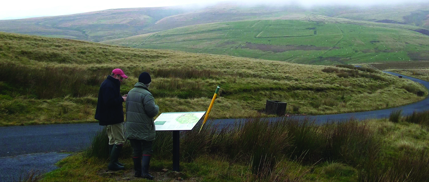 A couple looking at an information board with the Chew Green camp in the background