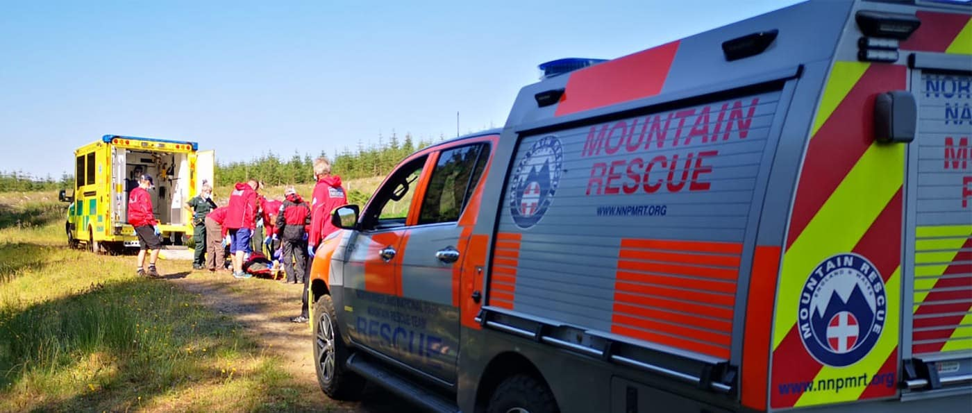 A mountain rescue vehicle and ambulance and volunteers looking after a patient