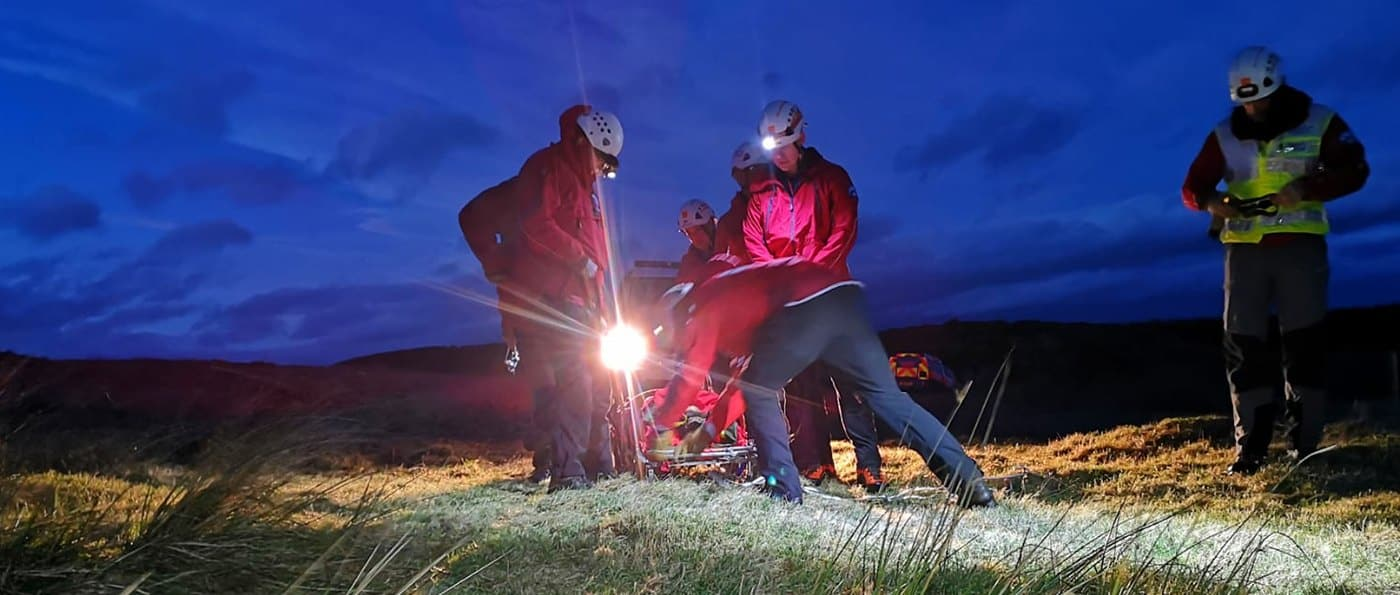 Three mountain rescue volunteers attending to a casuality