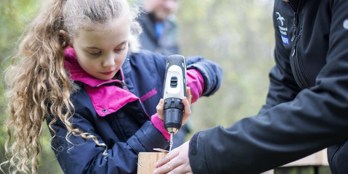 A young girl making a bat box with a National Park Ranger