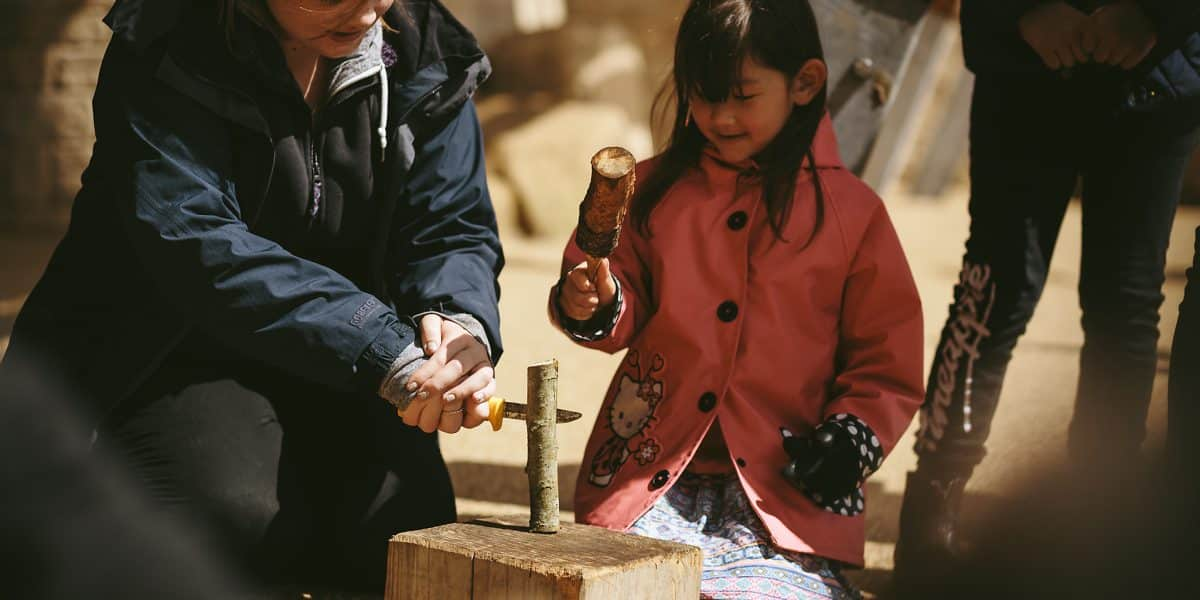 A young girl being helped to make a wooden musical instrument