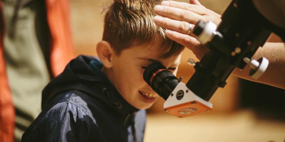 A young boy looking through a solar scope