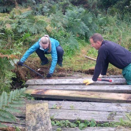 Volunteer Jessica Davison works with a National Park Ranger to repair a wooden bridge.