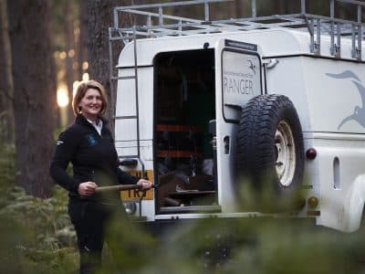 Head Ranger Margaret Anderson standing by a Land Rover in a forest.