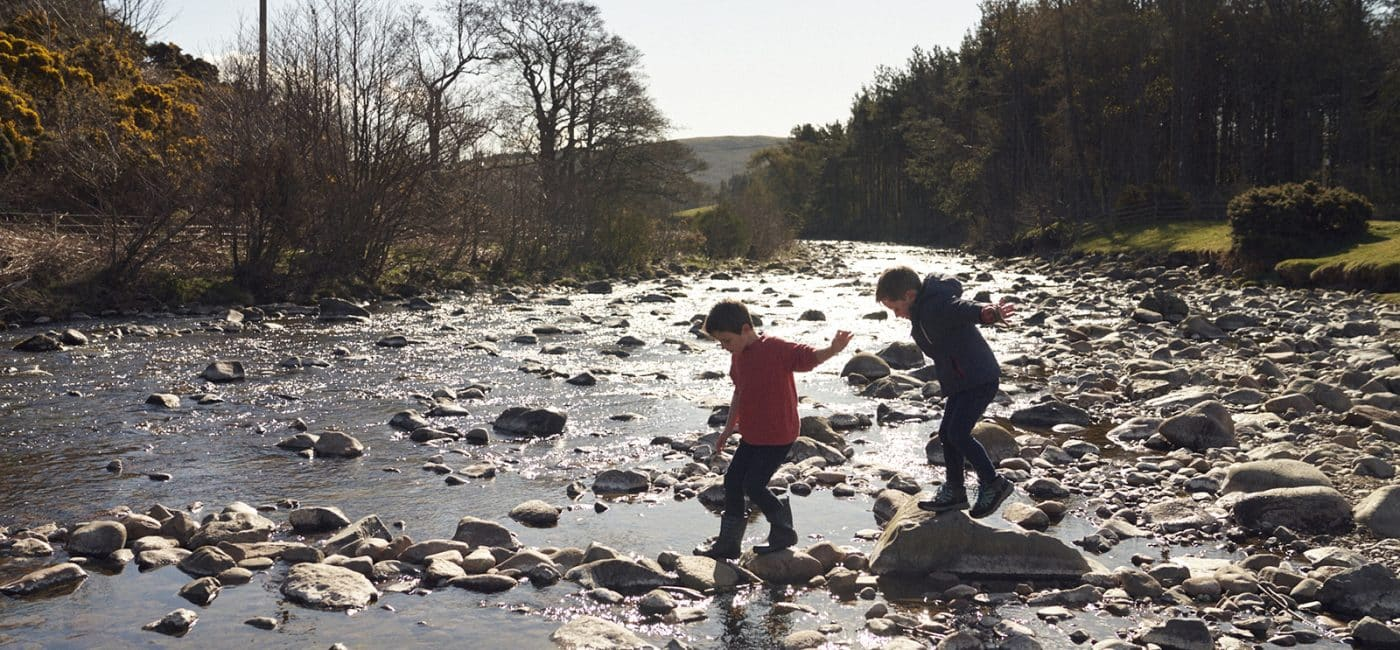 Two young boys walking across stepping stones in a river in the Northumberland National Park