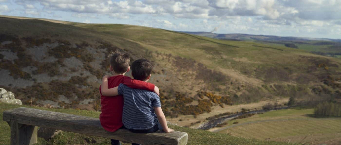 Two young boy sit arm in arm on a bench overlooking the Breamish Valley in Northumberland National Park
