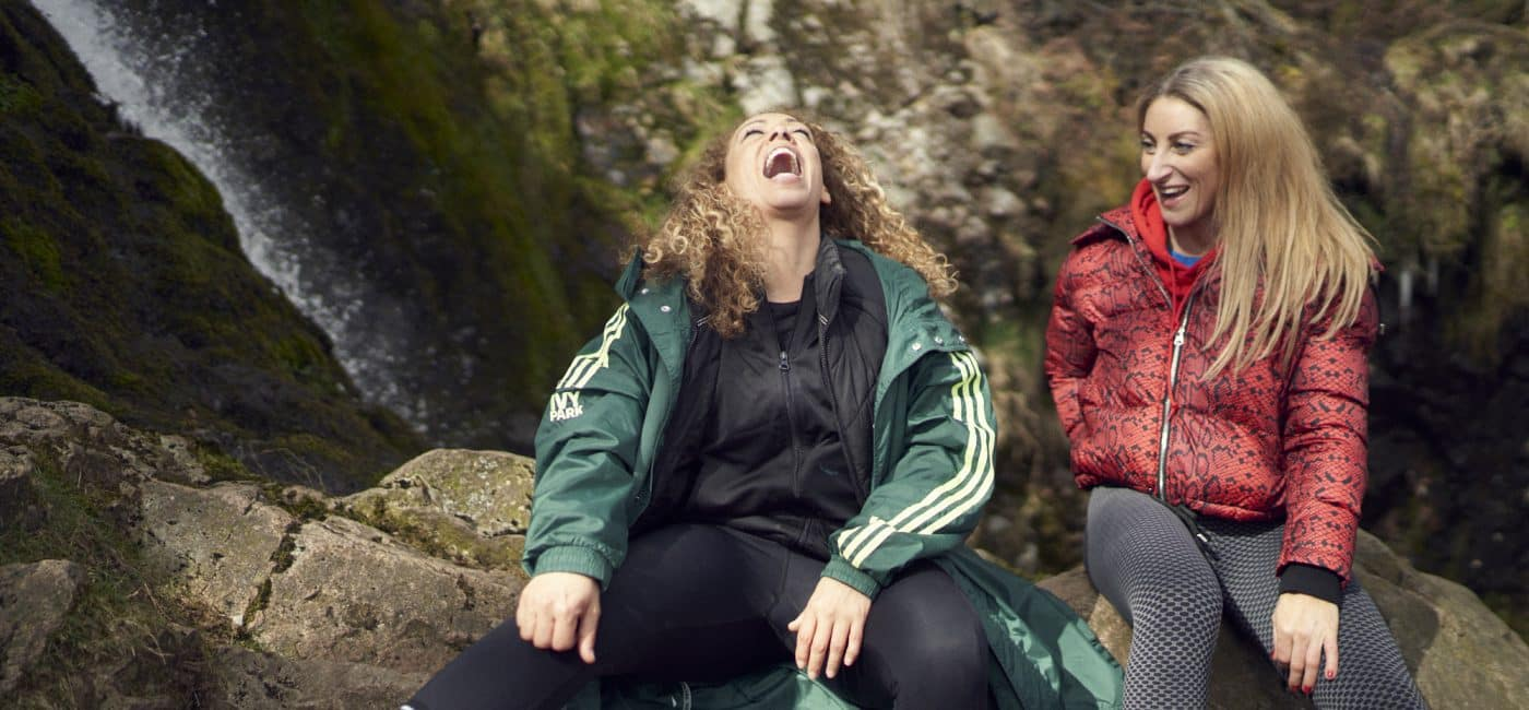 Two women, dressed in athletic clothing sit talking and laughing near a waterfall in Northumberland National Park
