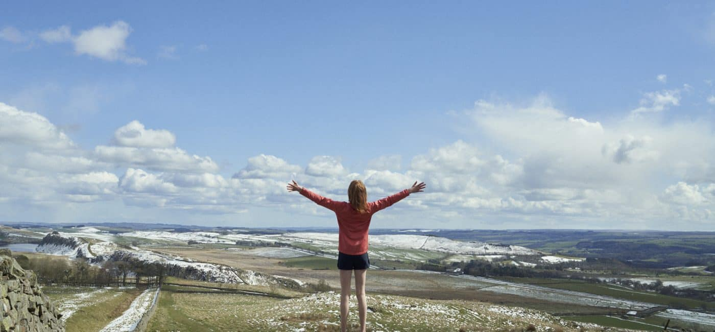 A young girl, arms outstretched, looks out over Hadrian's Wall in Northumberland National Park
