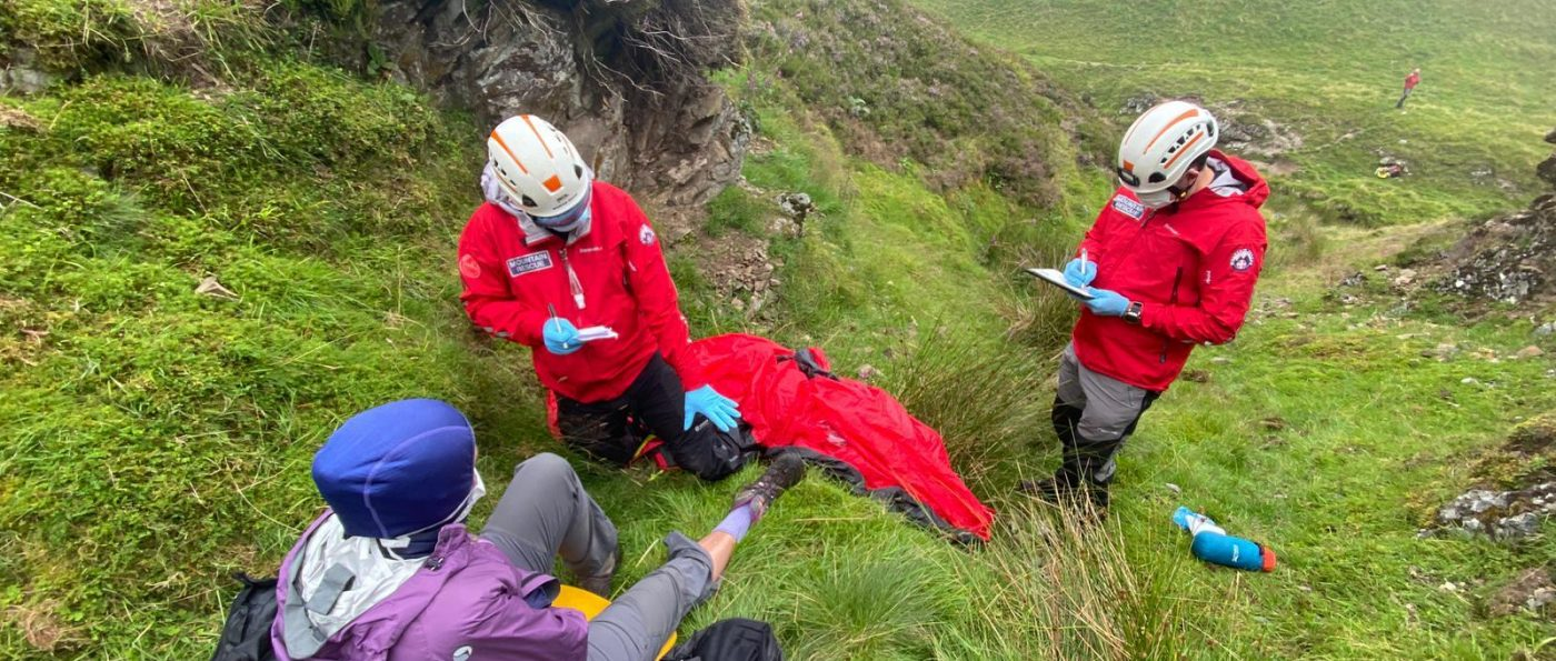 Two members of Mountain Rescue, wearing PPE masks help a member of the public down a step hill.