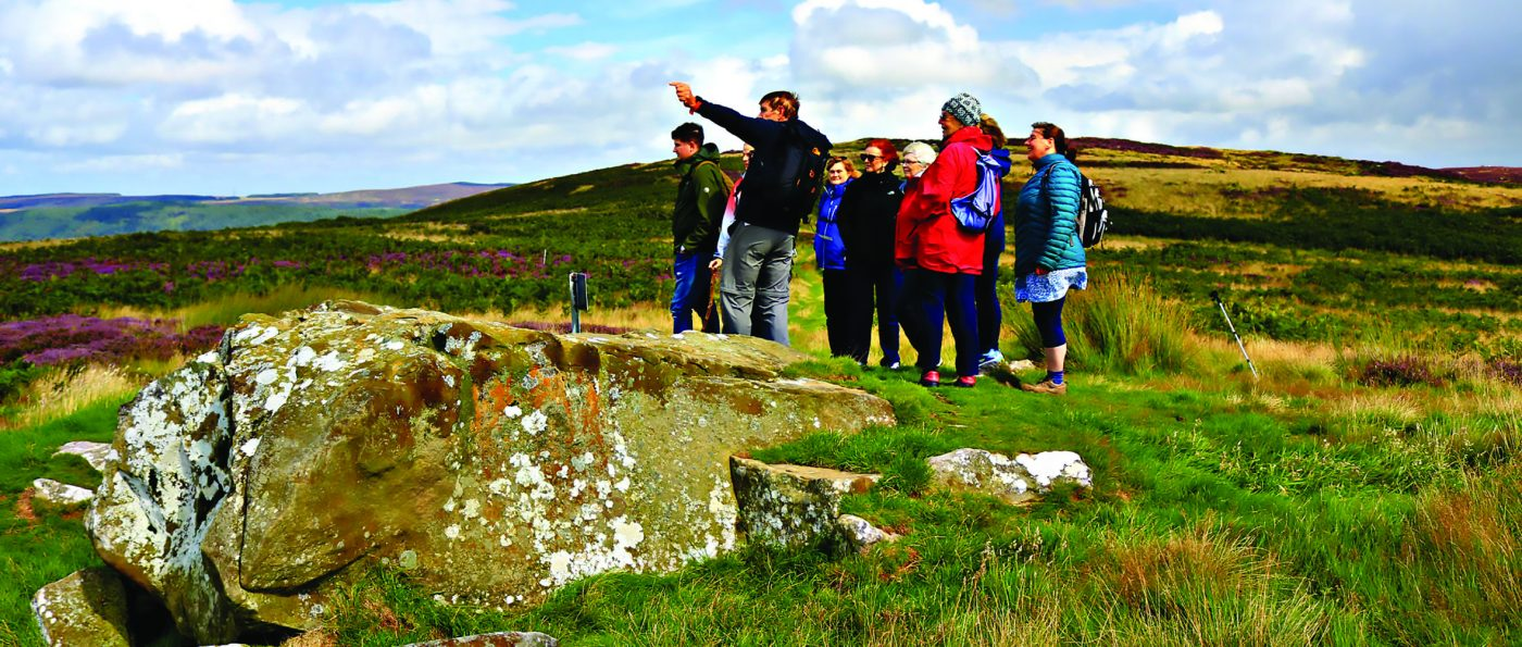 A guide leads a group of walkers at Lordenshaws in the Northumberland National Park