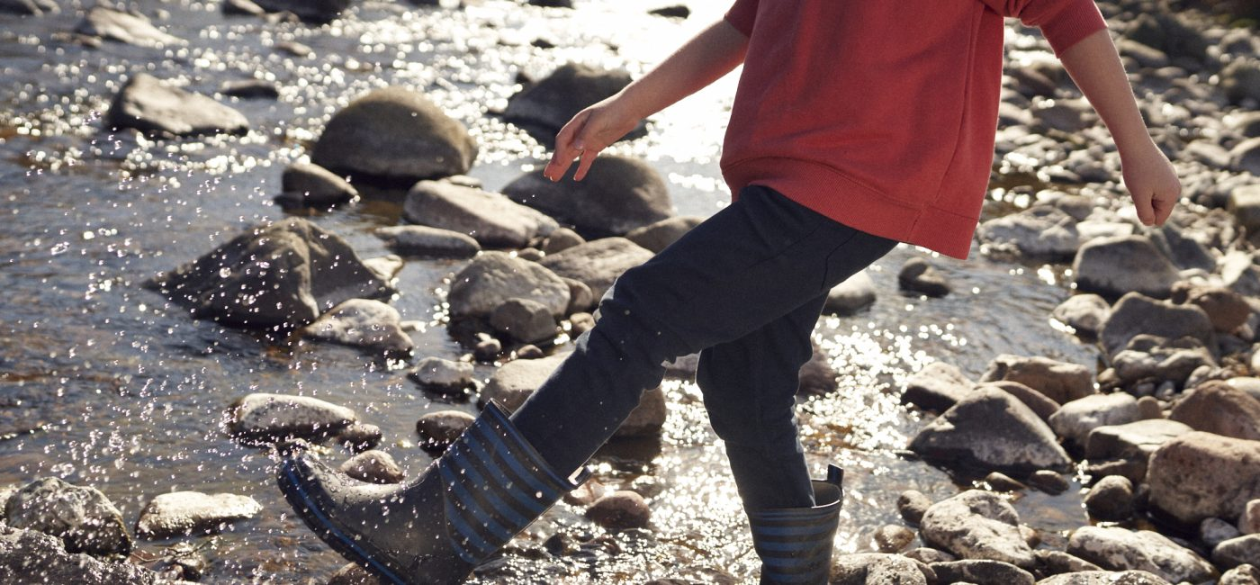A young boy wearing Wellington boots walking through a shallow river