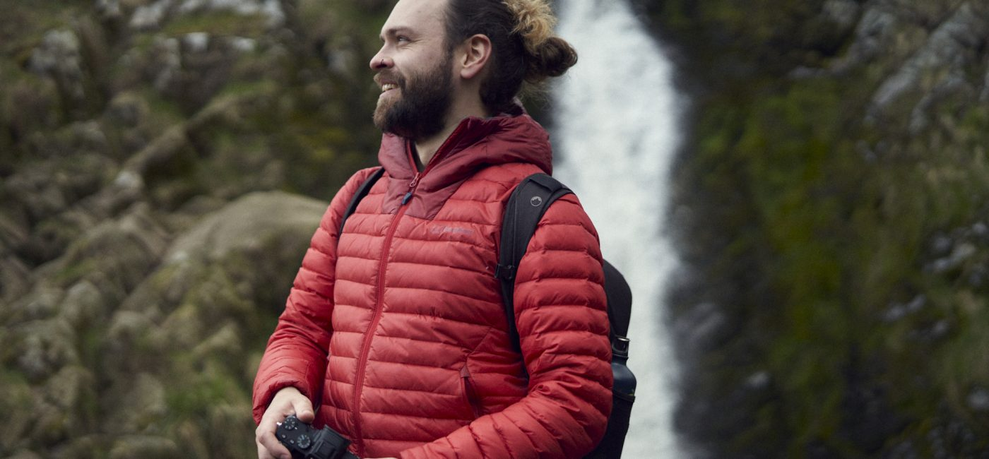 A young man in a red jacket holding a camera with a waterfall behind him