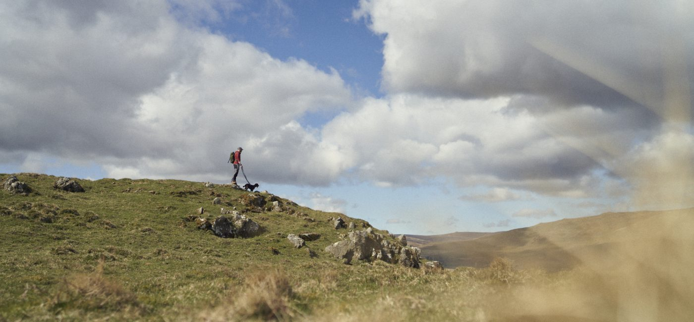 A man and a dog on a lead standing on top of a hill in the Breamish Valley