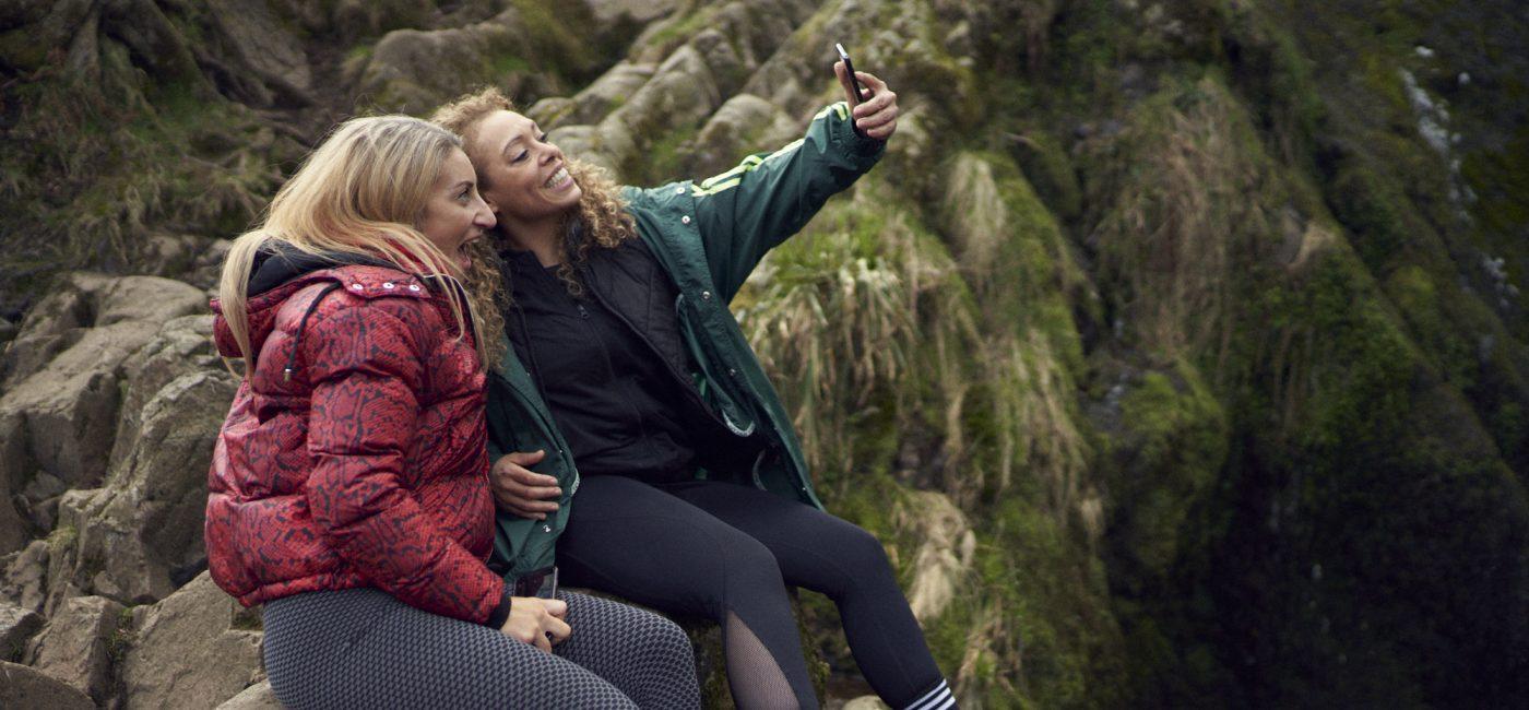 Two women wearing sporty clothing pose fora selfie, sat on a rocks.