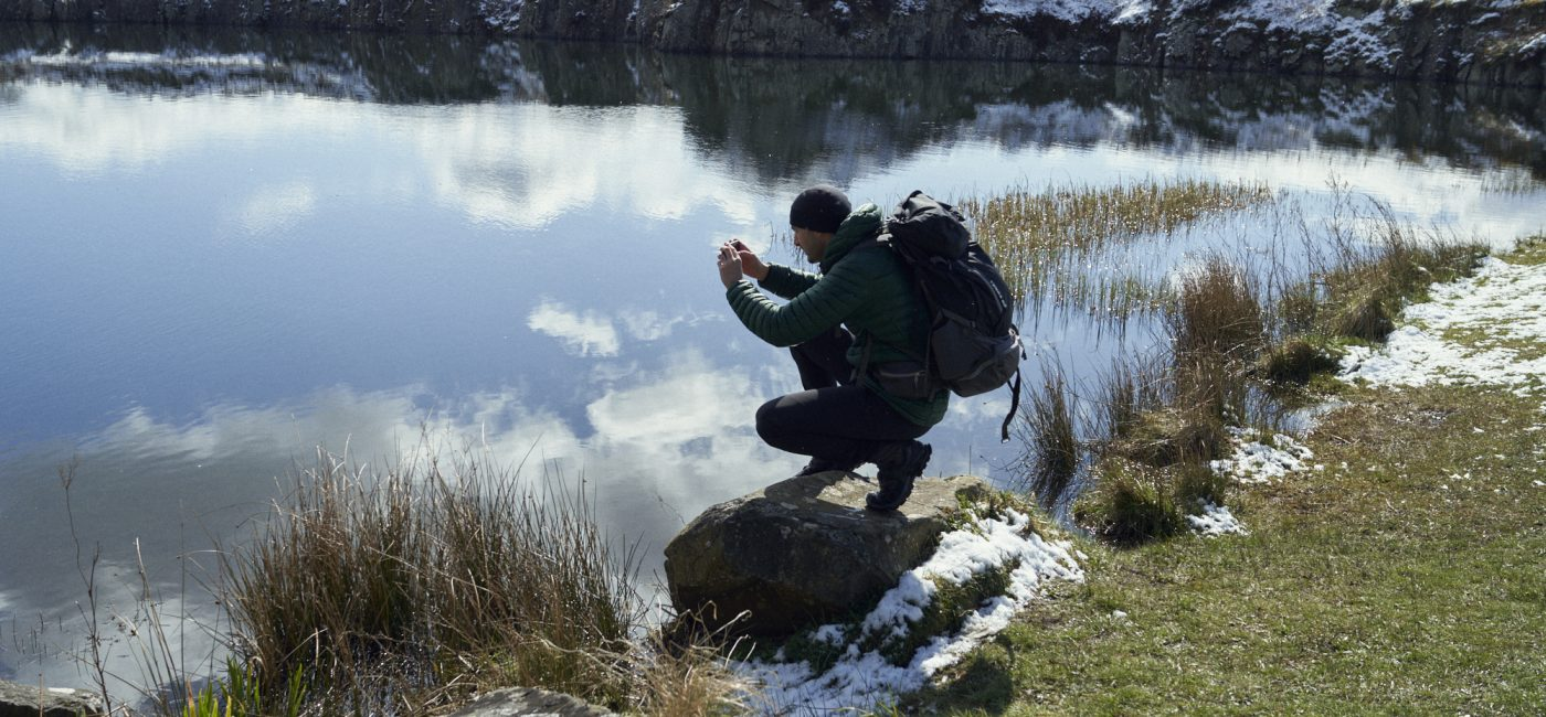 A young man crouches by a lake to take a photograph with his mobile phone