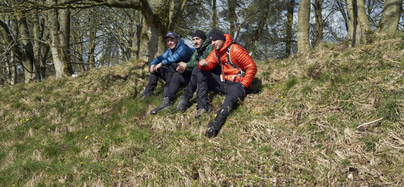 Three men sit on grassland