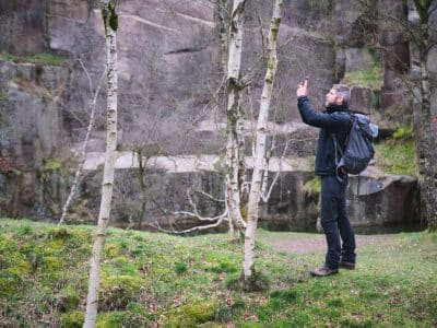 A man, weaing a rucksack, stands on the bank of a river holding his mobile photo out, to take a photograph.