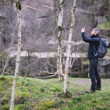 A man, wearing a rucksack, stands on the bank of a river holding his mobile photo out, to take a photograph.