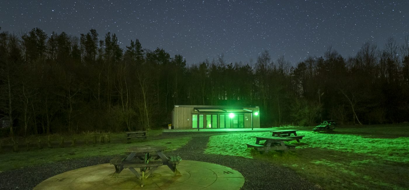 A building and stone circular area at Walltown Country at night with a sea of stars above