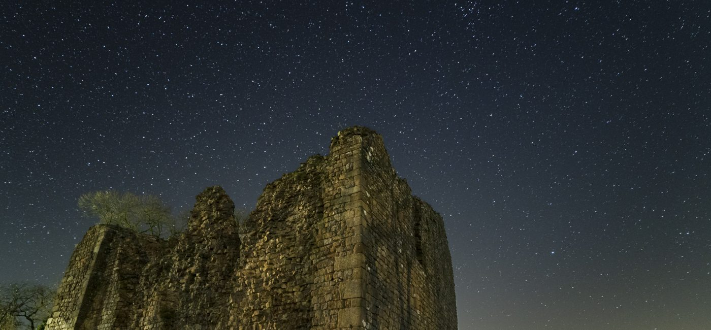 Thirlwall Castle at night with starry skies above