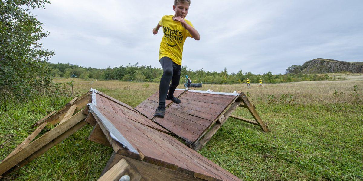 A boy running over a set of wooden steps