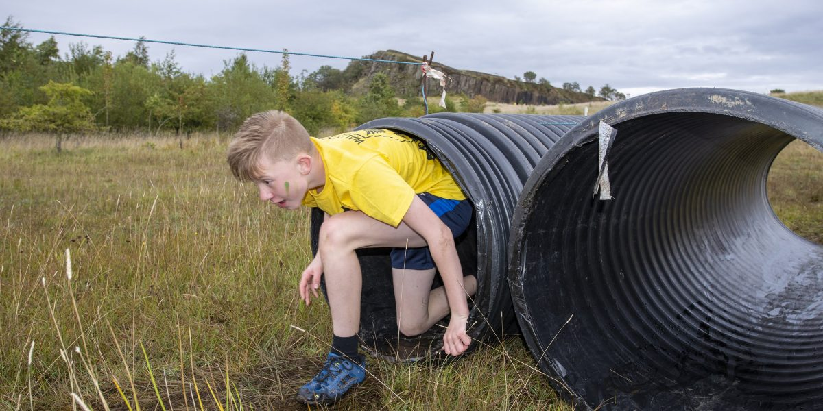 A young boy emerging from a plastic tunnel