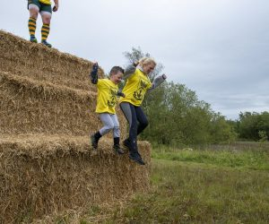 W young boy and women jumping down from a set of hay bales