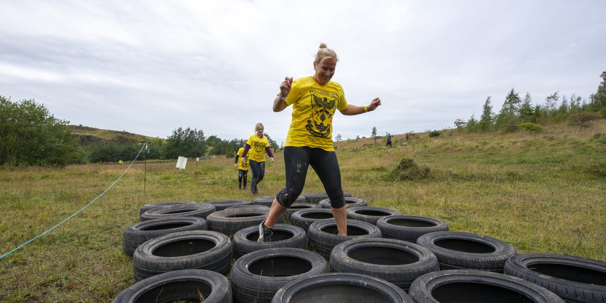 A women, followed by two others walking her way through a series of rubber tyres