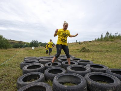 A women, followed by two others navgating her way through a series of rubber tyres