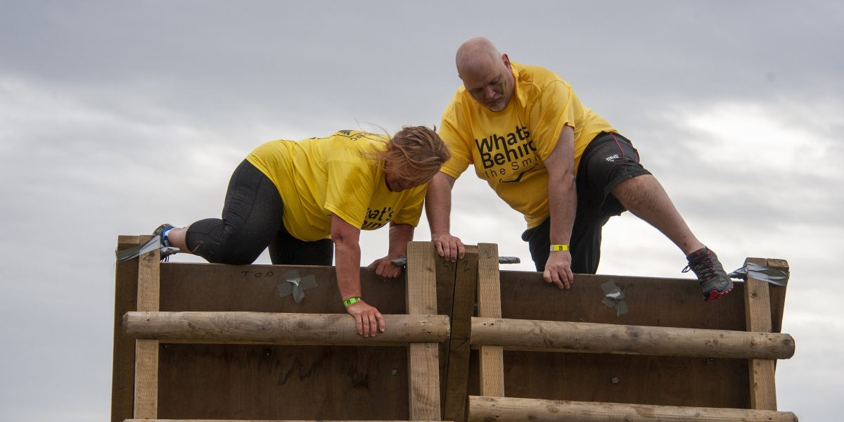 A man and woman climbing over a wooden obstacle