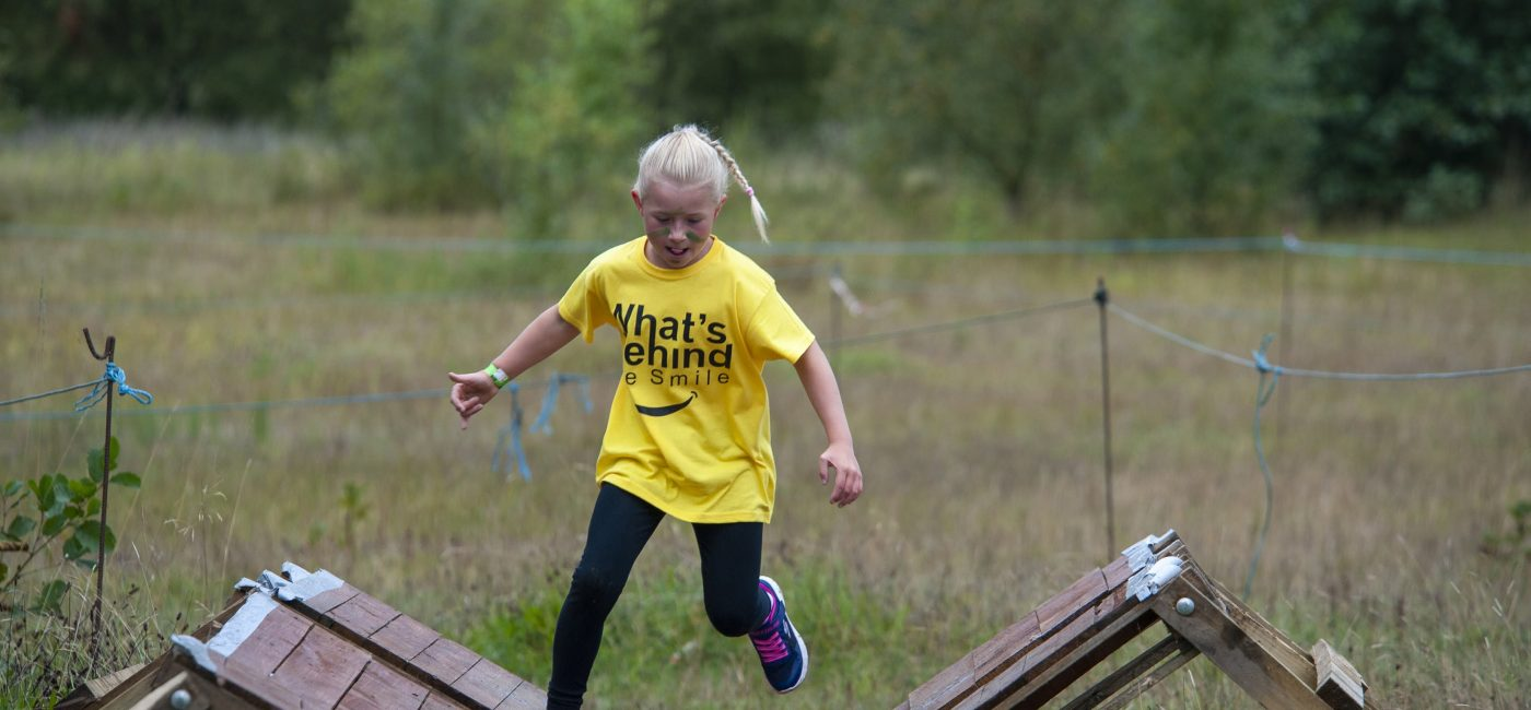 A young girl in a yellow t-shirt running over a wooden obstacle