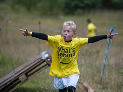 A boy crossing a race finishing line with his arms up high
